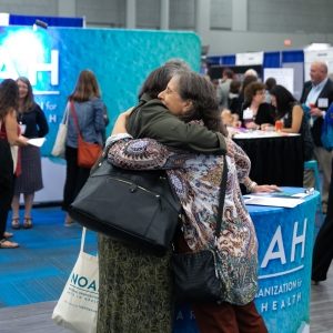 Conference goers embrace at the NOAH booth